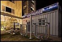 Public exercise equipment and buildings at night, Seogwipo. Jeju Island, South Korea ( color)