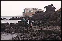 Businessmen on shore near Yongduam Rock, Jeju-si. Jeju Island, South Korea (color)
