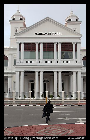 Man in suit crossing streets towards court building. George Town, Penang, Malaysia