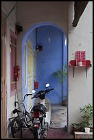 Motorcycle and altar outside townhouse. George Town, Penang, Malaysia