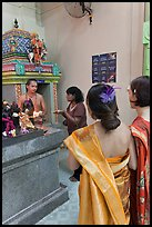 Holy man distributes fire to women, Sri Mariamman Temple. George Town, Penang, Malaysia ( color)
