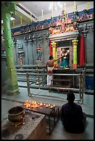 Holy man tends to altar, Hindu temple. George Town, Penang, Malaysia (color)