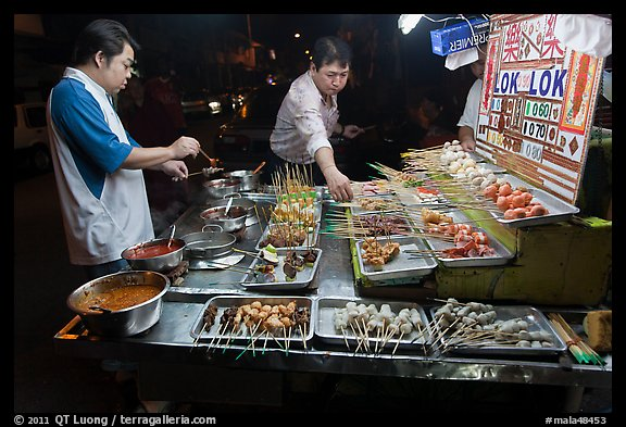 Men arranging skewers on hawker stall. George Town, Penang, Malaysia (color)