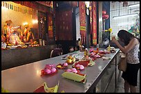 Woman Worshiping inside Chinese temple. George Town, Penang, Malaysia