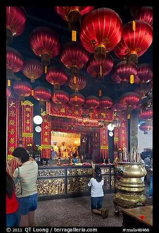 Woman in prayer, altar and lanters, Kuan Yin Teng temple. George Town, Penang, Malaysia (color)