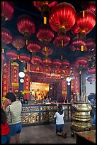 Woman in prayer, altar and lanters, Kuan Yin Teng temple. George Town, Penang, Malaysia