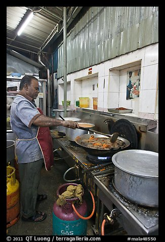 Man frying food in large pan. George Town, Penang, Malaysia (color)