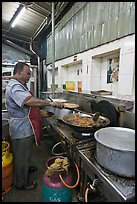 Man frying food in large pan. George Town, Penang, Malaysia ( color)