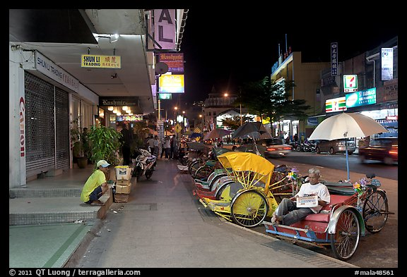 Cycle rickshaws lined on street at night. George Town, Penang, Malaysia