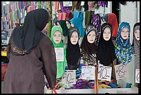 Woman in apparel store with islamic headscarves for sale. Kuala Lumpur, Malaysia (color)