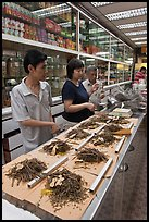 Chinese medicine herbs being packed on counter. Kuala Lumpur, Malaysia (color)