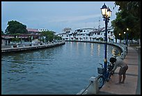 Woman locking bicyle on quay of Melaka River. Malacca City, Malaysia (color)