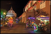 Illuminated trishaws on Town Square at night. Malacca City, Malaysia (color)