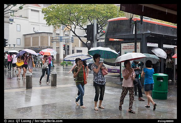 Women cross street of shopping area during shower. Singapore (color)
