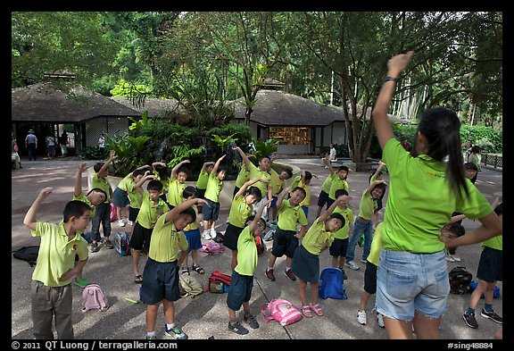 Schoolchildren doing gymnastics in  Singapore Botanical Gardens. Singapore