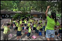 Schoolchildren doing gymnastics in  Singapore Botanical Gardens. Singapore ( color)