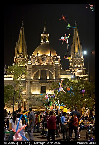 Children play with inflated balloons behind the Cathedral by night. Guadalajara, Jalisco, Mexico (color)