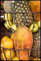 Boy peers from behind fruits offered at a juice stand, Tlaquepaque. Jalisco, Mexico (color)