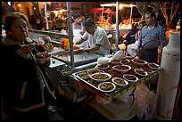 Woman eating by a street food stand , Tlaquepaque. Jalisco, Mexico
