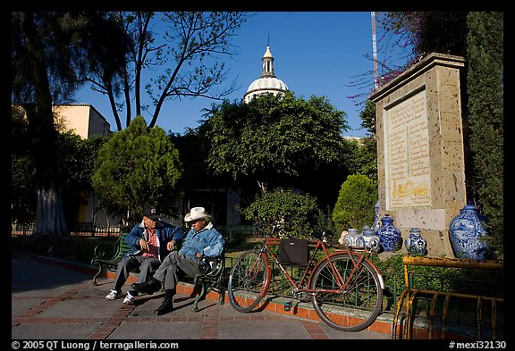 Men sitting in garden, with cathedral dome and ceramic monument, Tlaquepaque. Jalisco, Mexico (color)