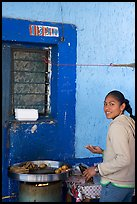 Woman preparing food outside a blue wall, Tonala. Jalisco, Mexico