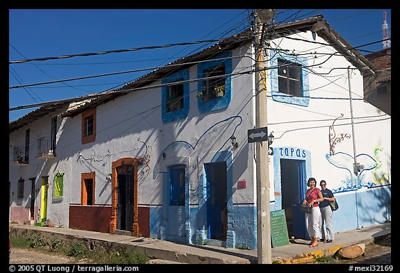 Two women outside of corner house with colorful door and window outlines, Puerto Vallarta, Jalisco. Jalisco, Mexico (color)