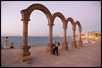 Boy standing by the Malecon arches at dusk, Puerto Vallarta, Jalisco. Jalisco, Mexico (color)