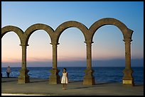 Girl standing by the Malecon arches at sunset, Puerto Vallarta, Jalisco. Jalisco, Mexico (color)