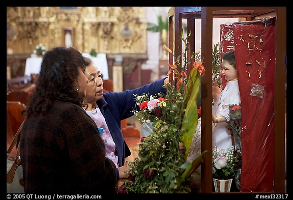 Women placing flowers in front of a Saint figure. Zacatecas, Mexico (color)