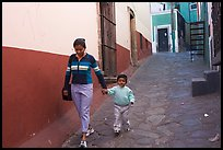 Woman and boy walking down an alleyway. Guanajuato, Mexico