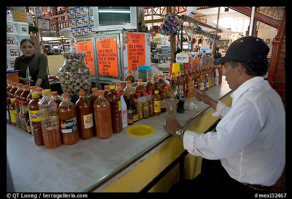 Man sitting at a booth offering a large variety of bottled chili. Guanajuato, Mexico (color)