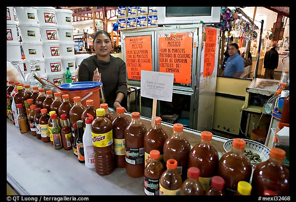 Woman at a booth with lots of chili bottles in Mercado Hidalgo. Guanajuato, Mexico (color)