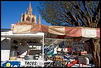 Taco stand on town plaza with cathedral in background. Mexico