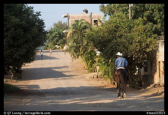 Man on horse going down a village street. Mexico (color)