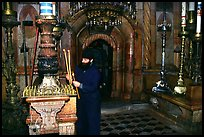 Christian Orthodox priest lighting candles. Jerusalem, Israel (color)