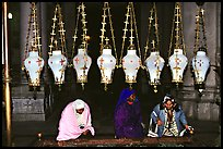 Women worshiping beneath hanging lamps inside the Church of the Holy Sepulchre. Jerusalem, Israel