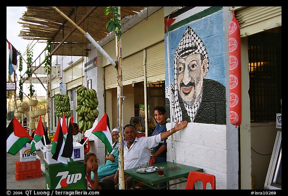Palestinian cafe owner pointing proudly to a painting of Yasser Arafat, Jericho. West Bank, Occupied Territories (Israel) (color)