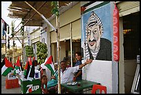 Palestinian cafe owner pointing proudly to a painting of Yasser Arafat, Jericho. West Bank, Occupied Territories (Israel)