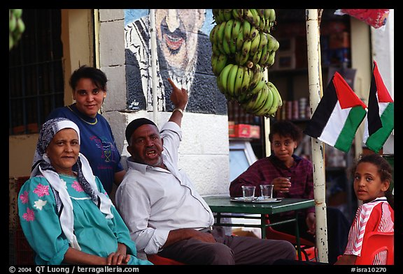 Palestinian head of family  pointing  to a mural of Yasser Arafat, Jericho. West Bank, Occupied Territories (Israel) (color)