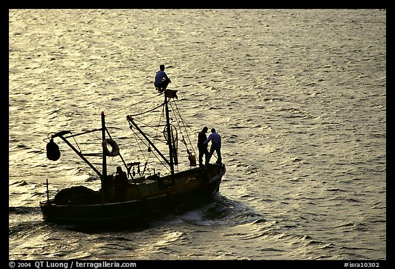 Small fishing boat silhouetted, late afternoon, Akko (Acre). Israel (color)