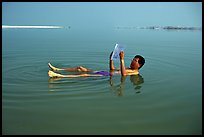Visitor reading while floating in the Dead Sea. Israel ( color)