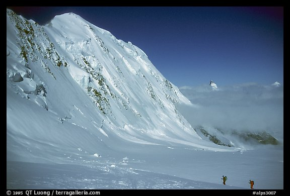 Backcountry skiers dwarfed by Liskam, Switzerland.  (color)