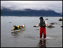Kayaker tows kayak near Scidmore Bay. Glacier Bay National Park, Alaska (color)
