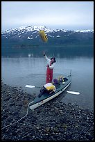 Kayaker unloading the kayak by throwing stuff sacks out. Glacier Bay National Park, Alaska