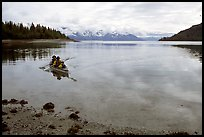 Kayakers paddle a double kayak in Hugh Miller Inlet. Glacier Bay National Park, Alaska (color)