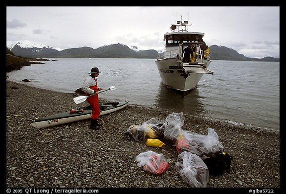 Kayaker standing with gear wrapped in plastic bags after drop-off. Glacier Bay National Park, Alaska