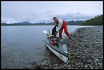 Kayaker loading gear into a double kayak. Glacier Bay National Park, Alaska (color)