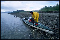 Kayaker unloading gear from a double kayak. Glacier Bay National Park, Alaska (color)