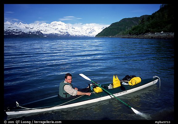 Kayaker sitting at a rear of a double kayak with the Fairweather range in the background. Glacier Bay National Park, Alaska (color)