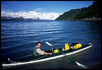 Kayaker sitting at a rear of a double kayak with the Fairweather range in the background. Glacier Bay National Park, Alaska